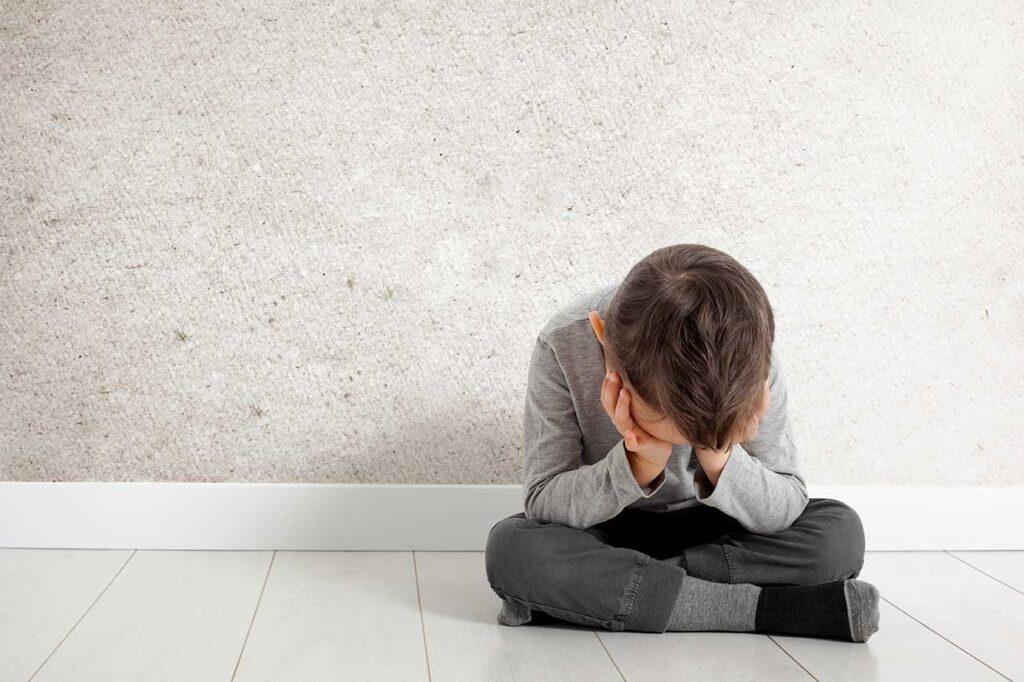 child whose depression is sitting floor
